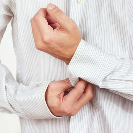 fastened: Hands a guy fastened the buttons on sleeve bright shirt close up
