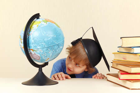 geographical: Little professor in academic hat looks at a geographical globe Stock Photo
