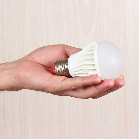 led lamp: Hand holding ecofriendly led bulb on a light wood background Stock Photo