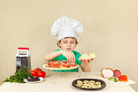 pizza crust: Young smiling boy in chefs hat puts a grated cheese on the pizza crust Stock Photo