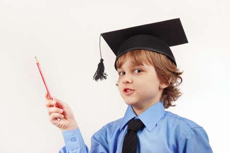 niños felices: Niño pequeño en el sombrero académico con lápiz sobre un fondo blanco