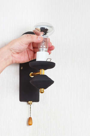 electrolier: Hand unscrews lightbulb in luminaire on a white wall