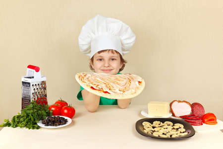 pizza crust: Little boy in chefs hat smeared with sauce on the pizza crust Stock Photo