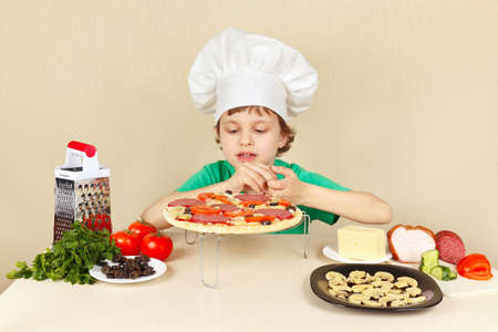 pizza crust: Young smiling boy in chefs hat puts the ingredients on the pizza crust