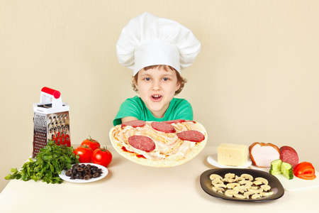 pizza crust: Little funny chef puts sausage on the pizza crust