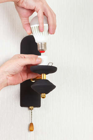 Hand unscrews led bulb in luminaire on a white wall