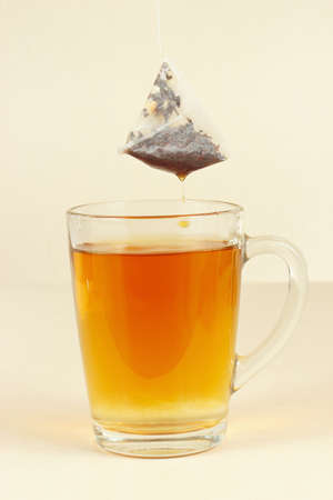 Tea bags over the glass with brewed tea Imagens
