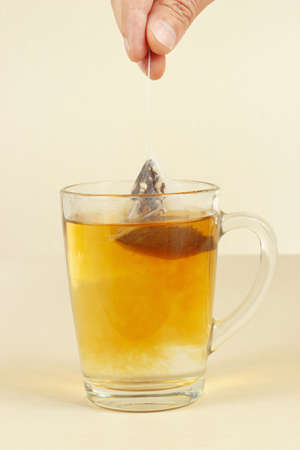 Hand brews tea bag in a glass of hot water