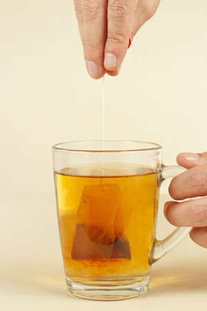 Hands brewed strong fresh tea in a glass