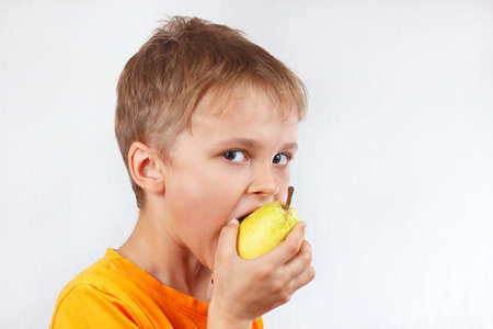 Little boy in a orange shirt eating a yellow pear Reklamní fotografie
