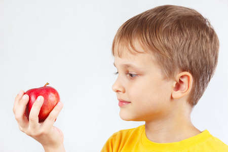 yellow shirt: Little boy in a yellow shirt with red apple