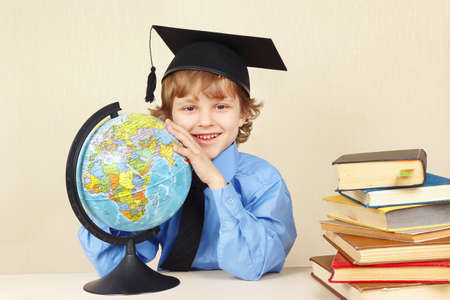 country boy: Little smiling boy in academic hat with a globe among the old books