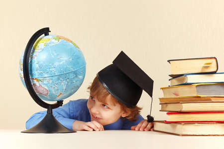 geographical: Little boy in academic hat looks at a geographical globe