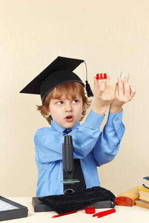 conducts: Little smart boy in academic hat conducts research with the microscope