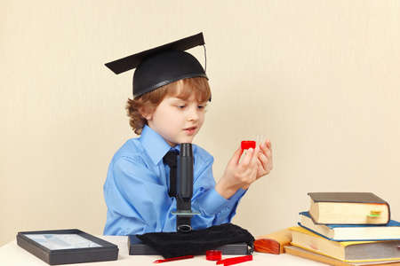 conducts: Little boy in academic hat conducts research with the microscope