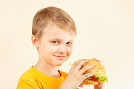 eating dinner: Little funny boy with a tasty sandwich