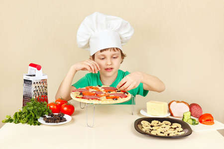 pizza crust: Little funny chef puts the ingredients on the pizza crust Stock Photo