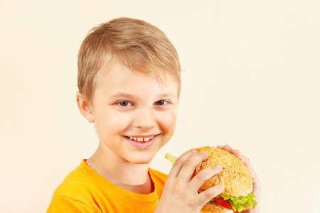 alimentacion sana: Pequeño muchacho sonriente con una sabrosa hamburguesa