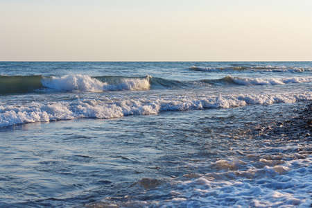 rocks water: Tranquil surf waves on the beach against the clear sky