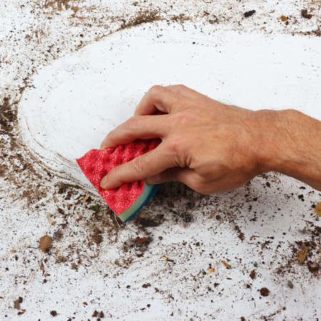 very dirty: Hand with sponge cleans a very dirty surface