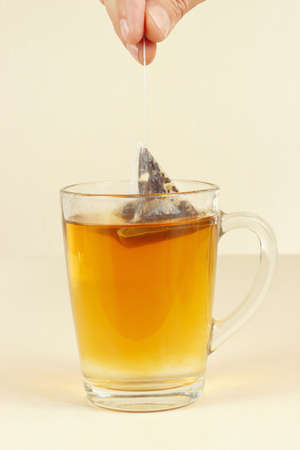 Hand brews pyramid tea bag in a glass of hot water