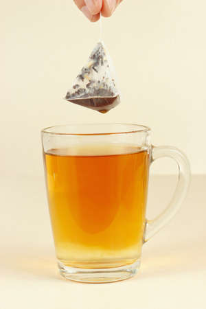 Hand pulls the tea bag from the cup of tea