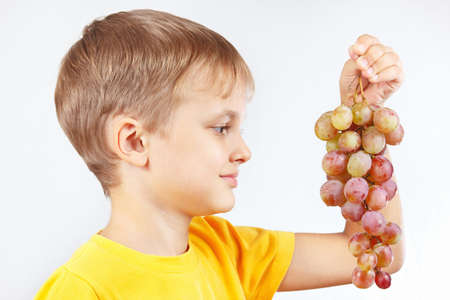 yellow shirt: Young boy in a yellow shirt with a grape Stock Photo