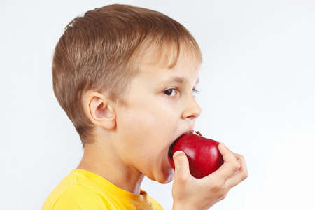 yellow shirt: Young boy in a yellow shirt eating a red apple