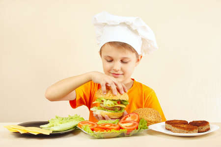 cook: Young smiling chef shows how to cook a hamburger Stock Photo