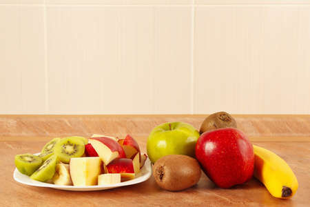 sliced fruit: Fresh whole and sliced fruit on the kitchen table
