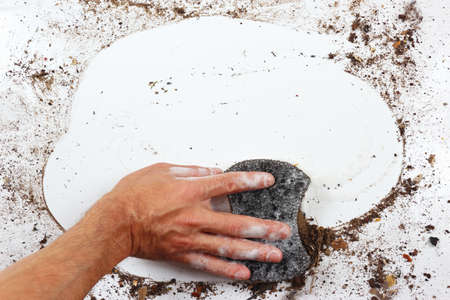 very dirty: Hand with wet black sponge cleans a very dirty surface
