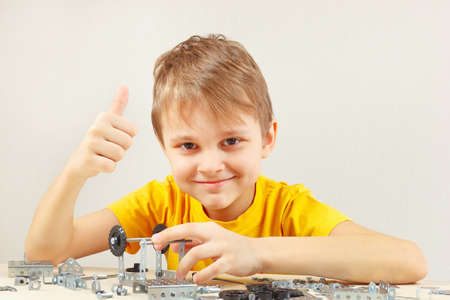 Young engineer plays with mechanical constructor at the table