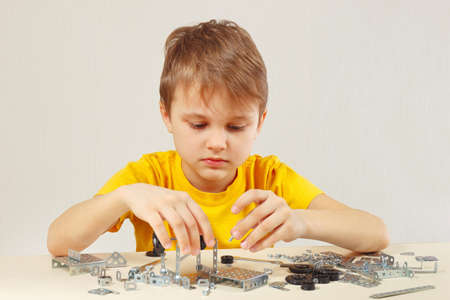 constructor: Little engineer plays with mechanical constructor at the table Stock Photo