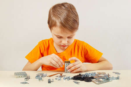 constructor: Little boy plays with mechanical constructor at the table Stock Photo