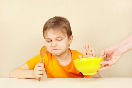 reluctance: Little cute boy refuses to eat a porridge Stock Photo