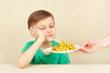 feed the poor: Little cute unhappy boy refuses to eat a fries