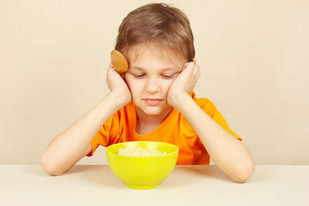 reluctance: Little boy does not want to eat a porridge Stock Photo