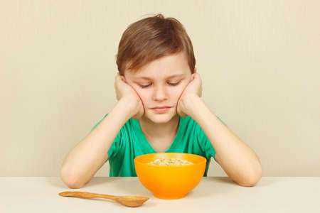 feed the poor: Little displeased boy does not want to eat a porridge