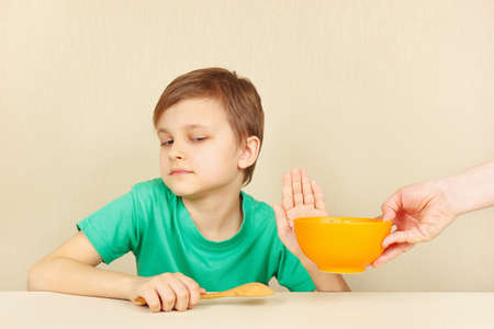 reluctance: Little discontented boy refuses to eat a porridge