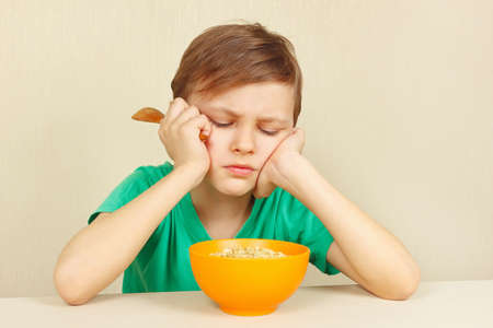 reluctance: Little discontented boy does not want to eat a cereal