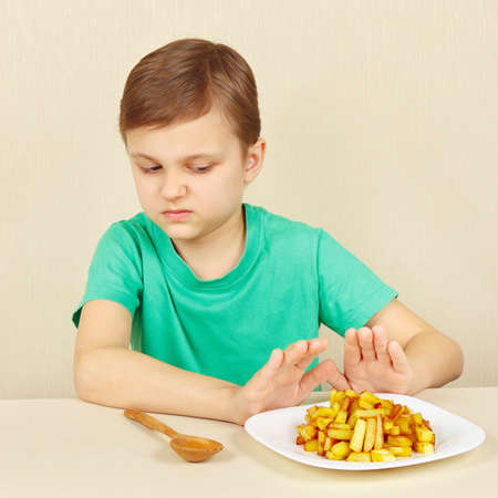 reluctance: Little boy does not want to eat a fried potatoes