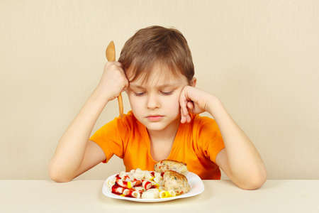 discontented: Little discontented boy does not want to eat a pasta with cutlet