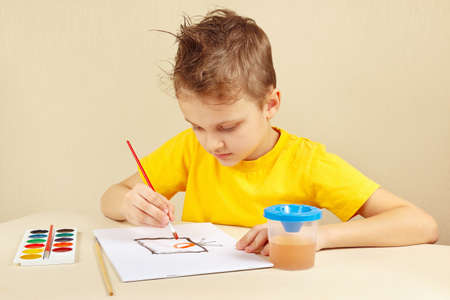 beginner: Beginner artist in a yellow shirt painting with watercolors