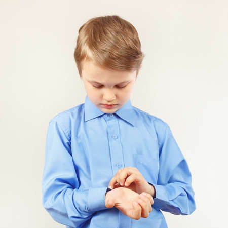 fastened: Little cute boy fastened the buttons on sleeve his bright shirt
