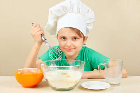 little dough: Little boy in chef hat prepares the dough for baking the cake