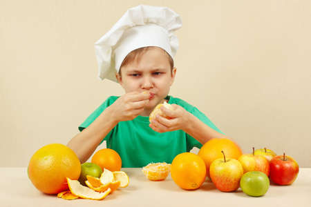 acidic: Little funny boy eat acidic orange at the table with fruits