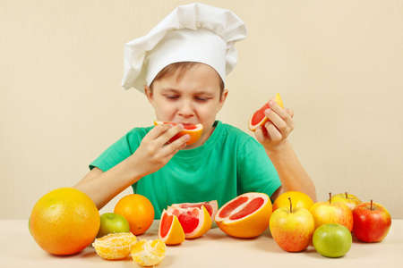 acidic: Little funny boy eat acidic grapefruit at the table with fruits