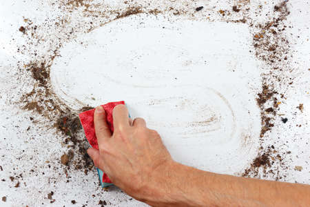 heavily: Hand with sponge cleans a heavily dirty surface