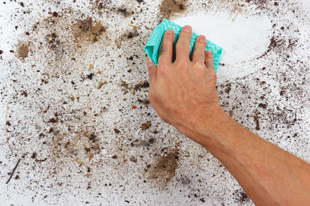 wiping: Hand with cloth wiping a dirty surface