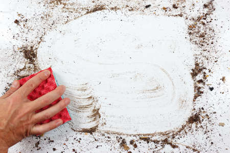 very dirty: Hand with red sponge wiping a very dirty surface Stock Photo